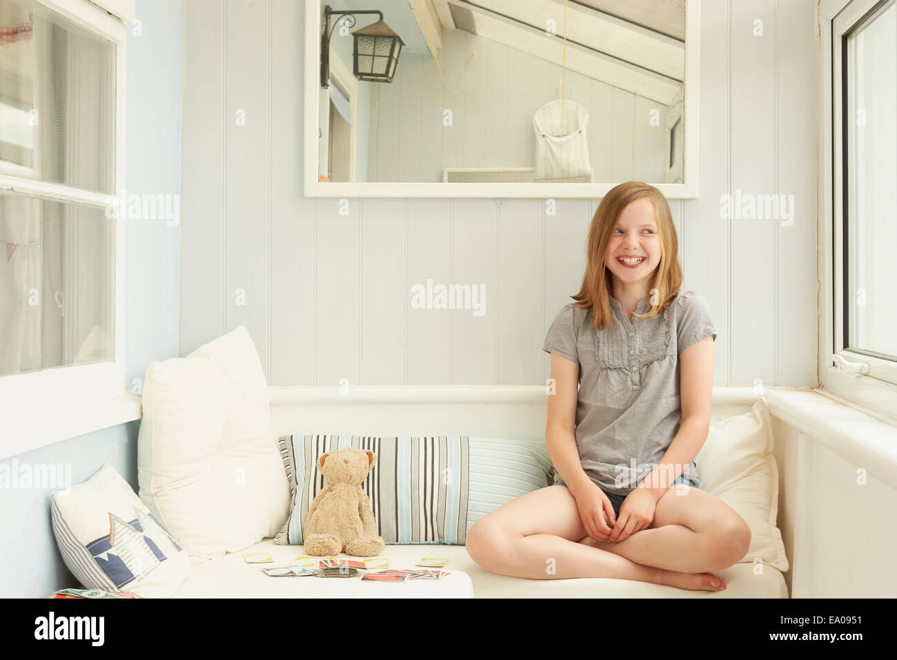 Portrait of girl looking sideways in holiday apartment porch - Stock Image