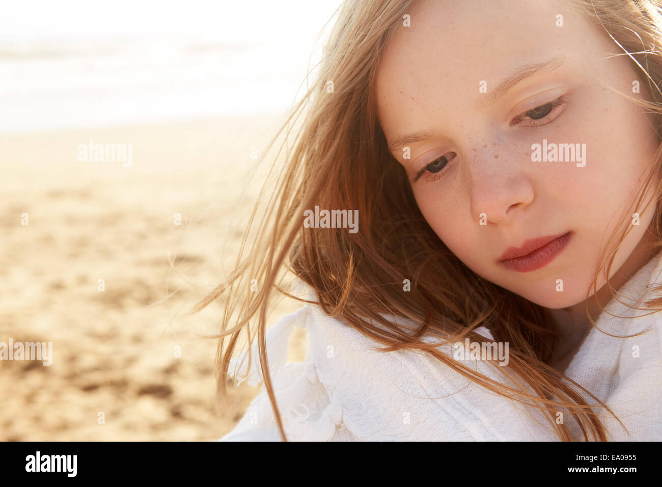 Close up portrait of girl wrapped in blanket on beach - Stock Image