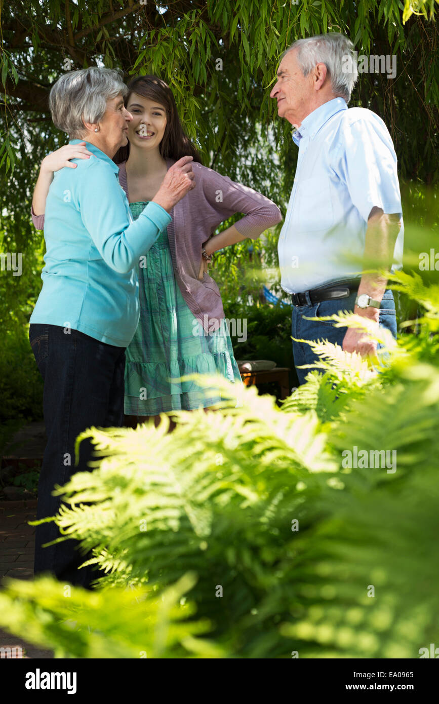 Grandparents and granddaughter having conversation in garden - Stock Image