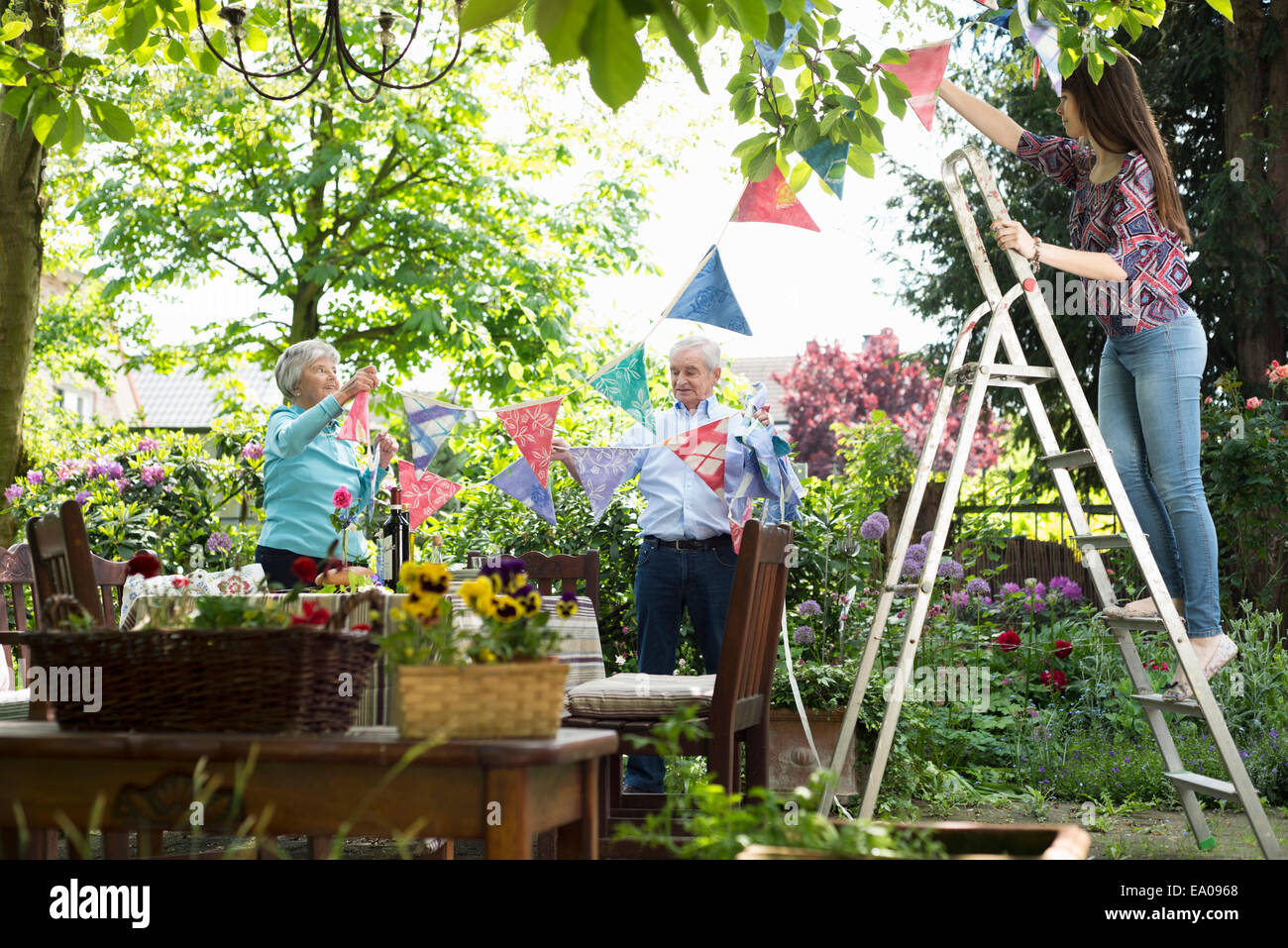 Grandparents and granddaughter hanging up bunting - Stock Image