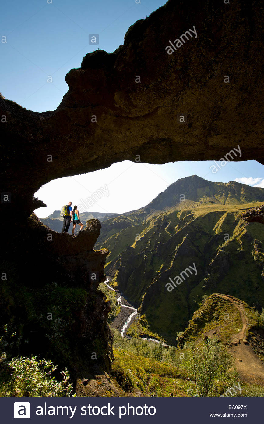 Couple standing in arch on way up to Fimmvordurhals Pass above Thorsmork Valley, Thorsmork, South Iceland, Iceland - Stock Image