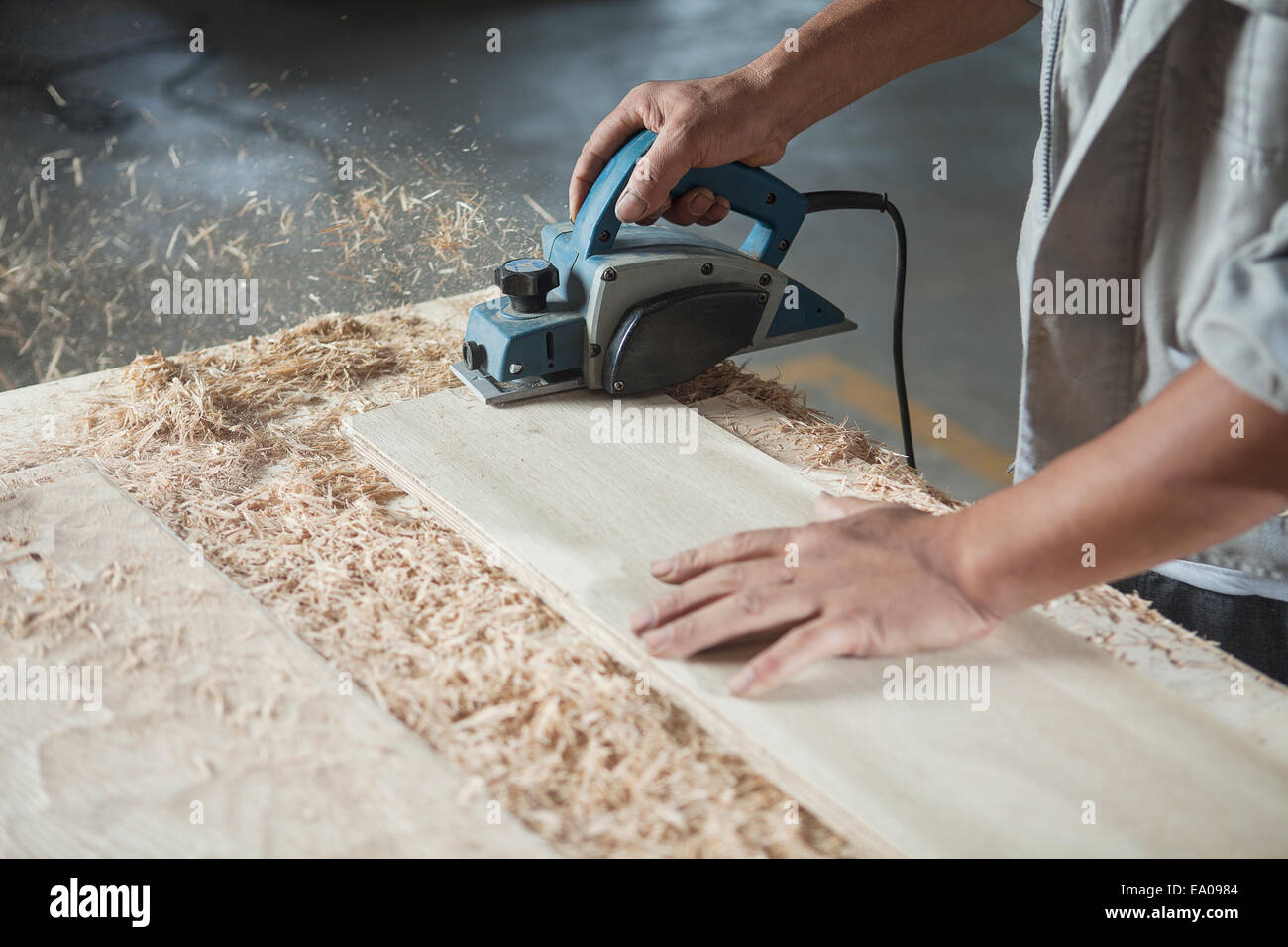 Carpenter cutting wood plank in factory, Jiangsu, China - Stock Image