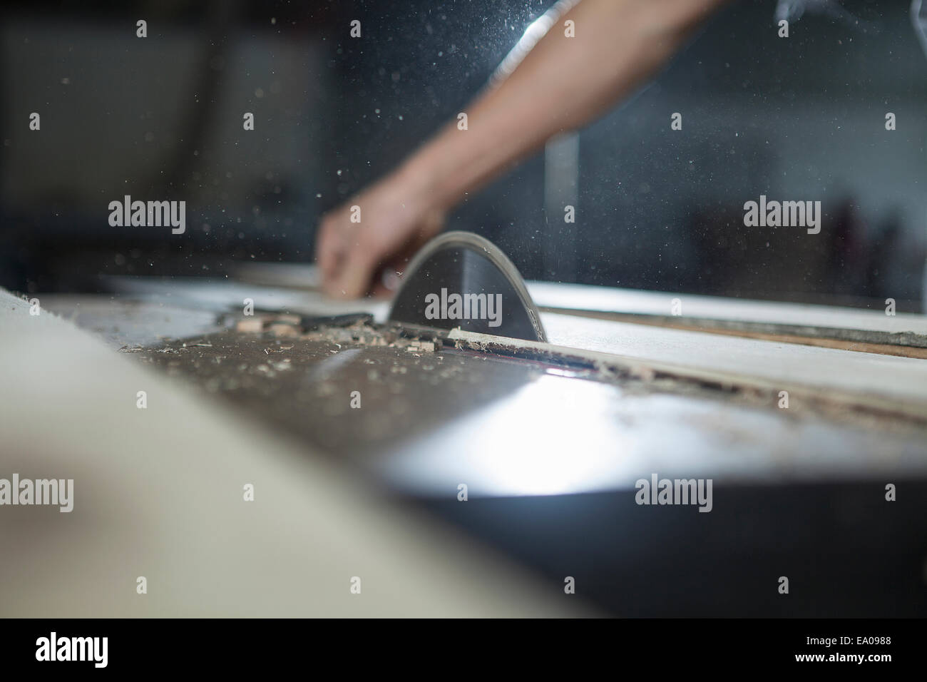 Carpenter cutting wood plank with electric saw in factory, Jiangsu, China - Stock Image