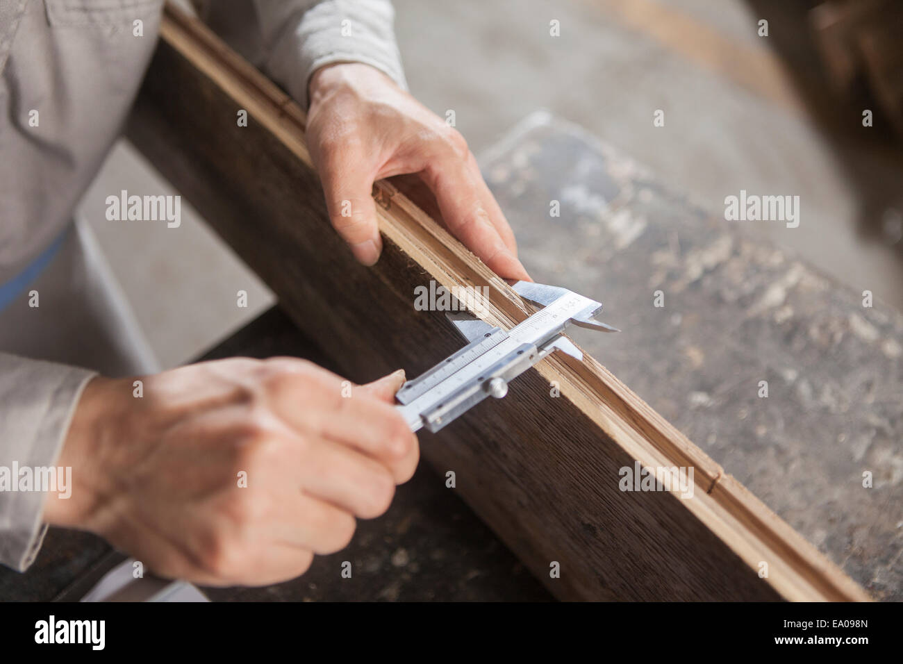 Carpenter measuring wood plank with vernier caliper in factory, Jiangsu, China - Stock Image