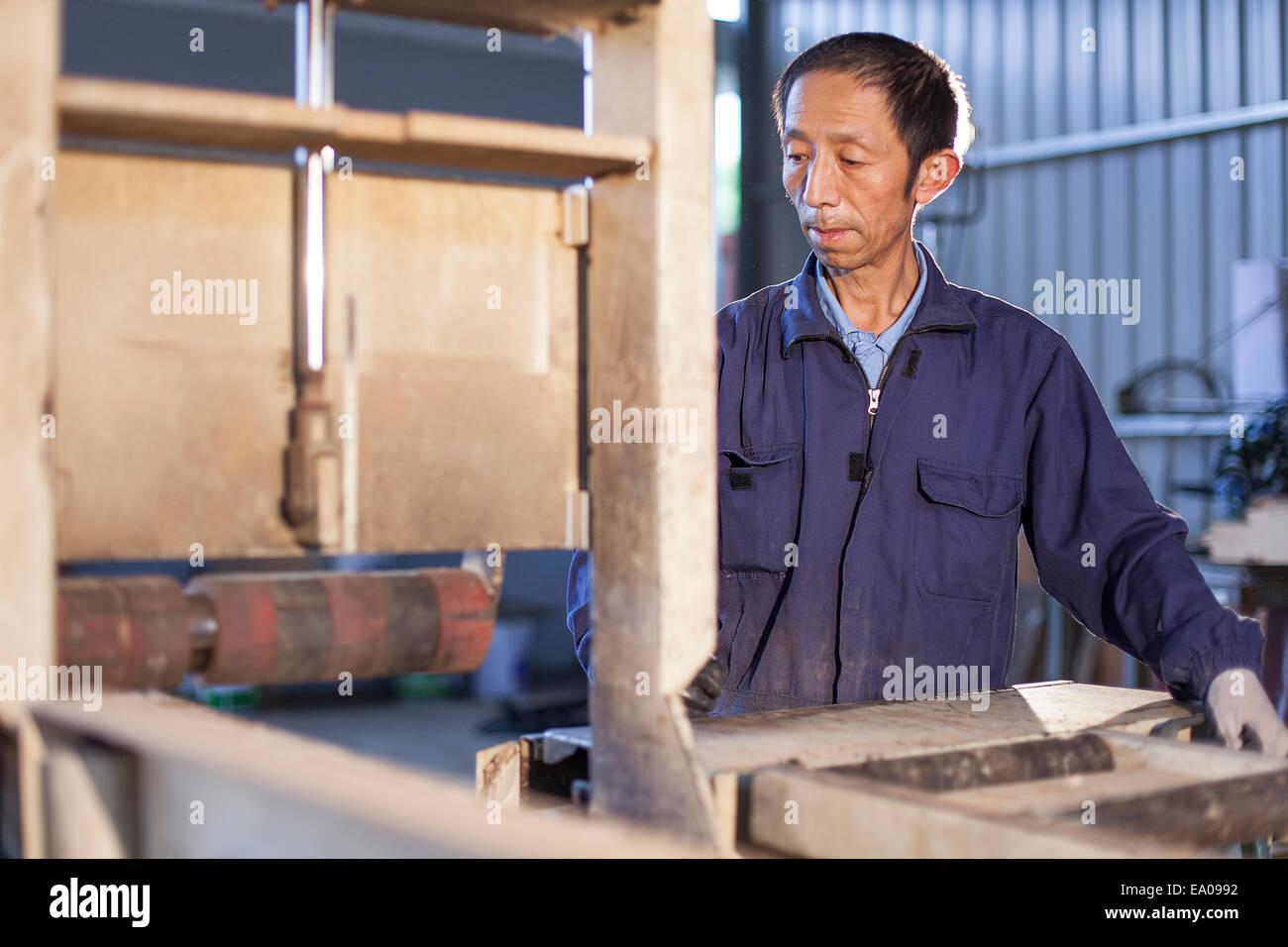 Carpenter working on wood flooring in factory, Jiangsu, China - Stock Image