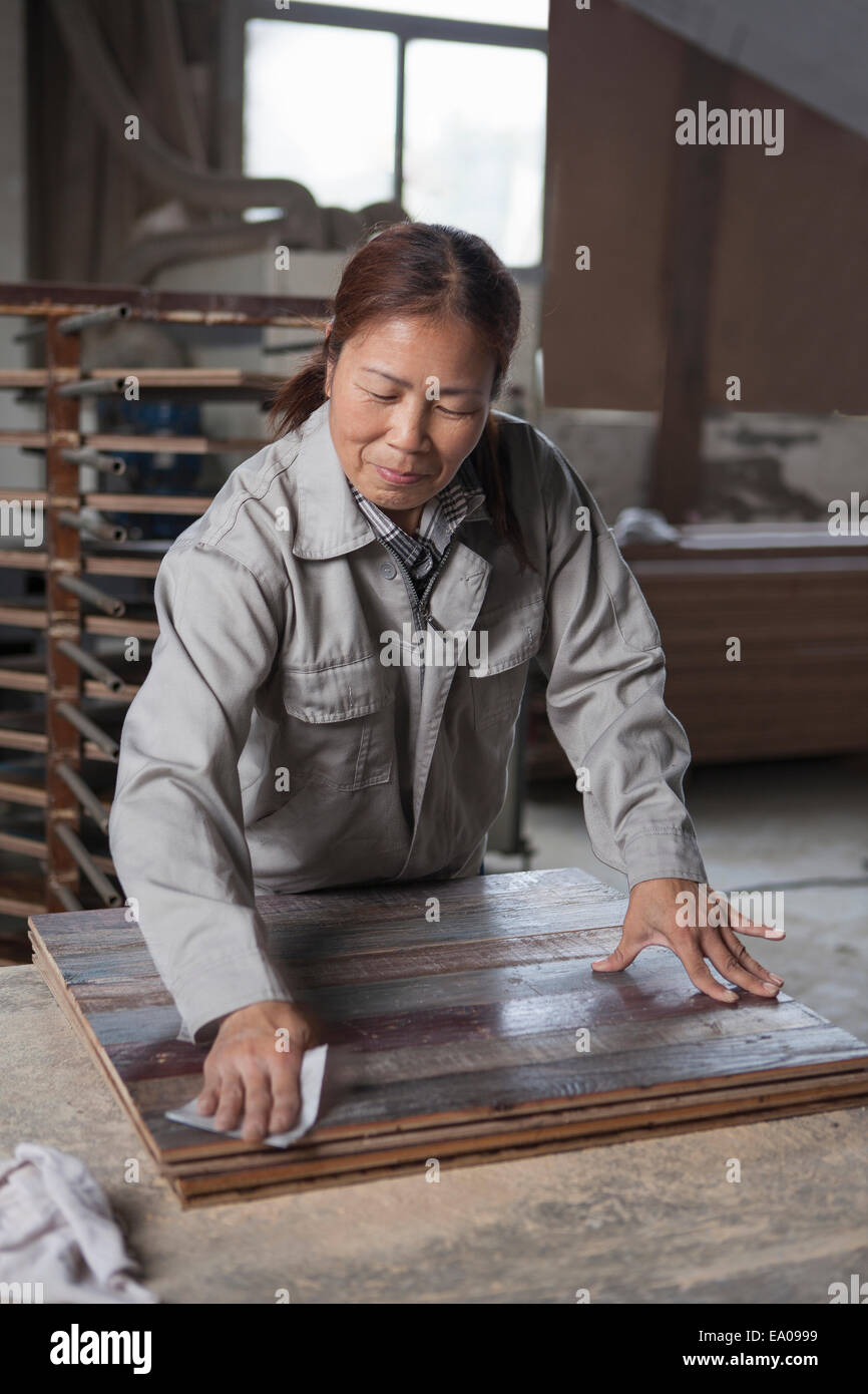 Carpenter smoothing surface of wood plank with sandpaper in factory, Jiangsu, China - Stock Image
