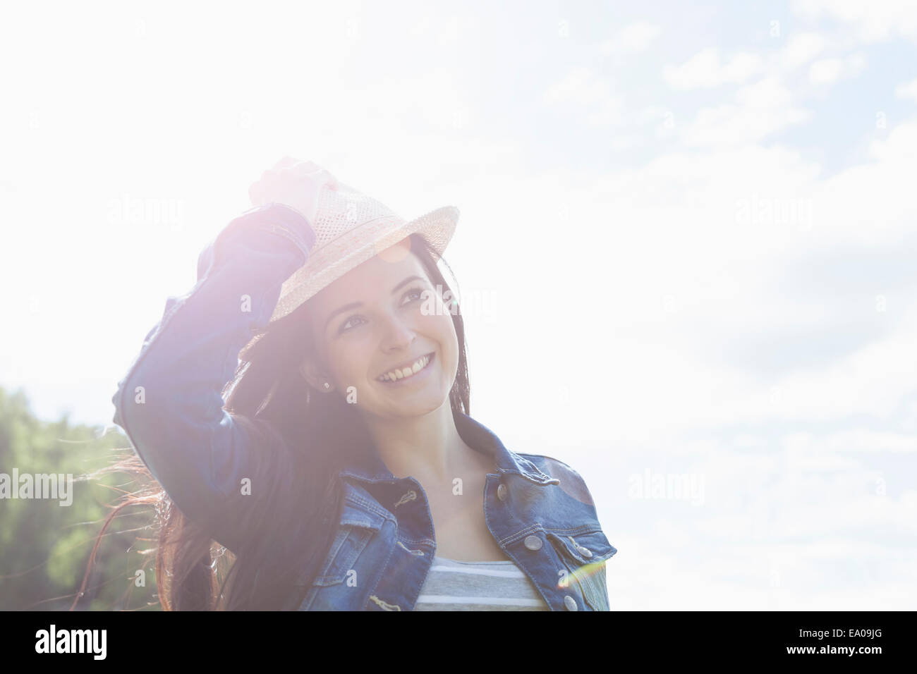 Young woman smiling, holding onto hat - Stock Image
