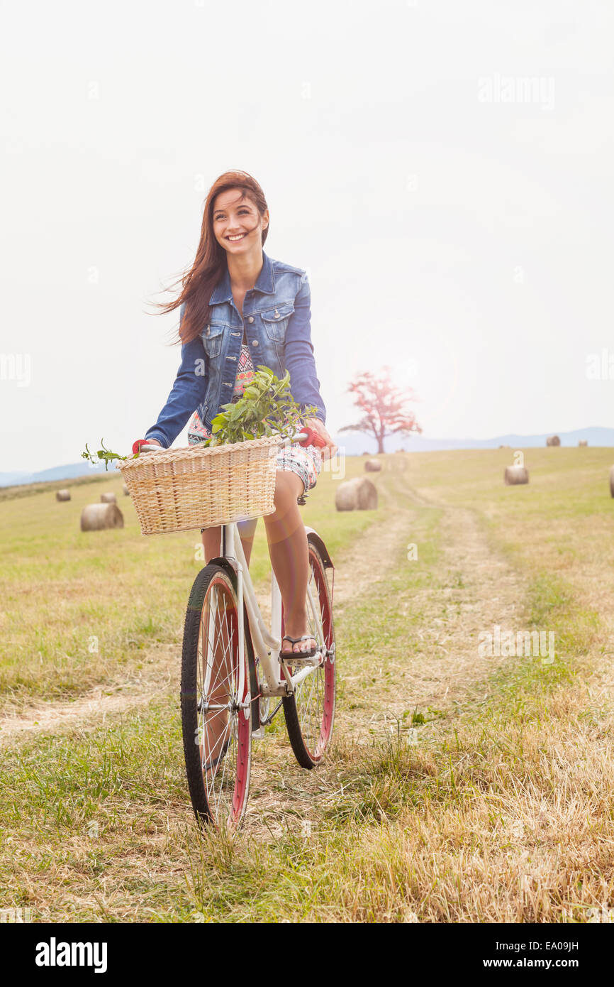 Teenager riding bicycle on field, Roznov, Czech Republic Stock Photo
