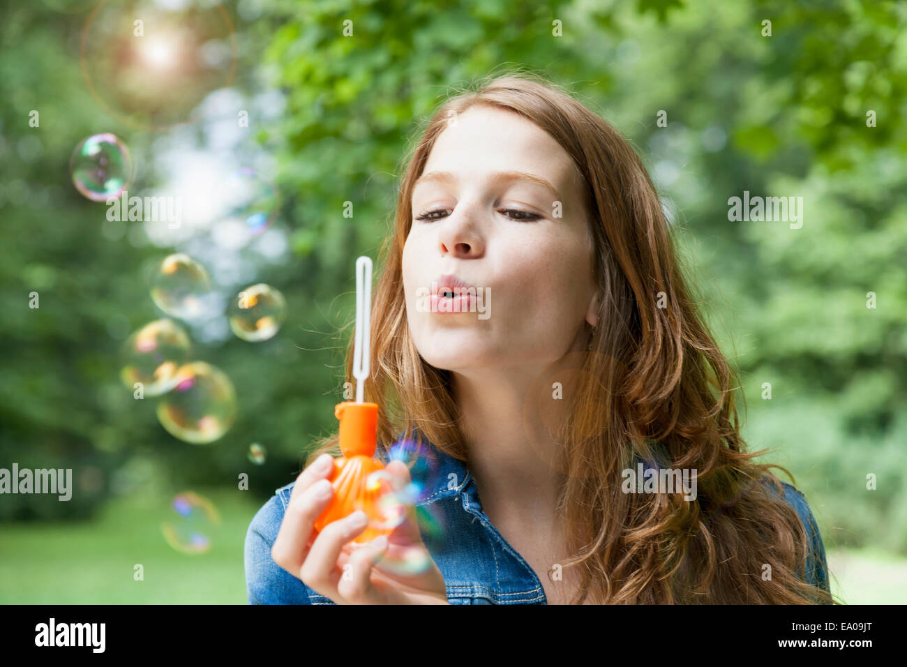 Young woman blowing bubbles in garden - Stock Image