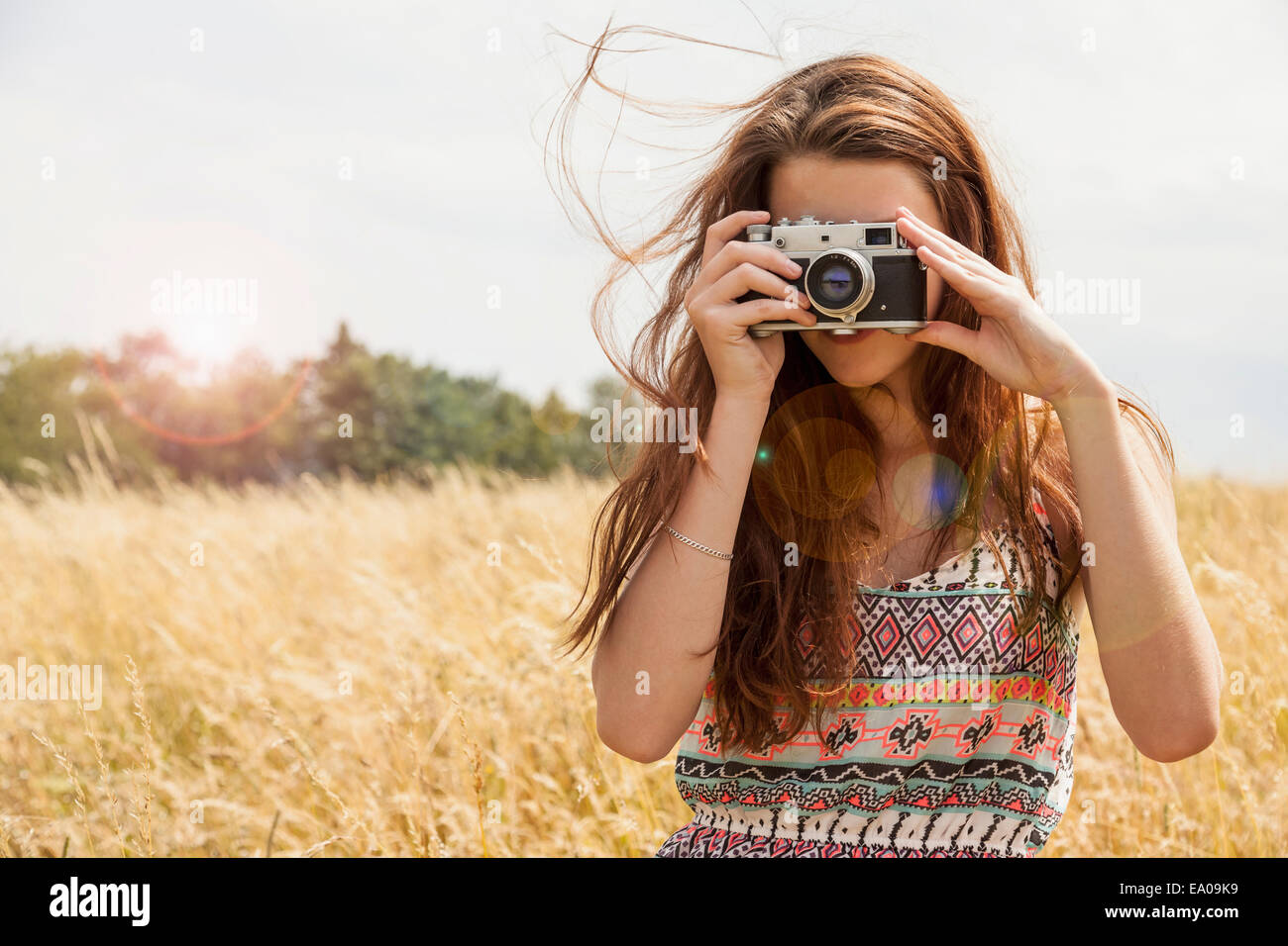 Young woman taking photo with vintage camera in field - Stock Image