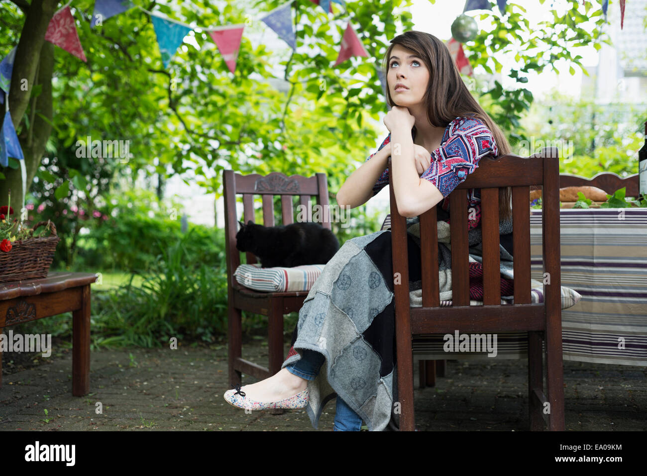 Pensive young woman sitting in garden - Stock Image