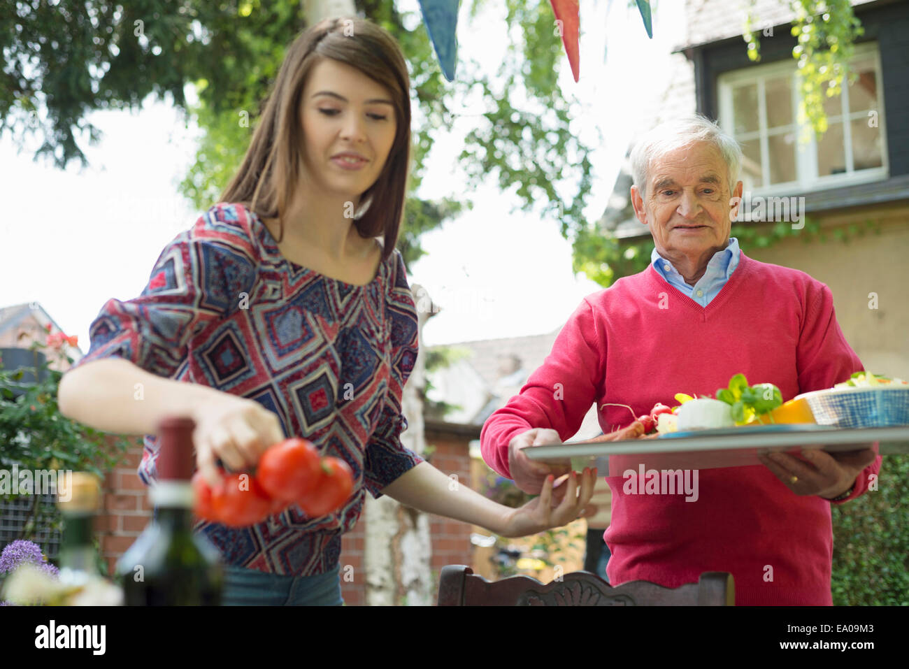 Grandfather carrying tray with granddaughter setting table - Stock Image