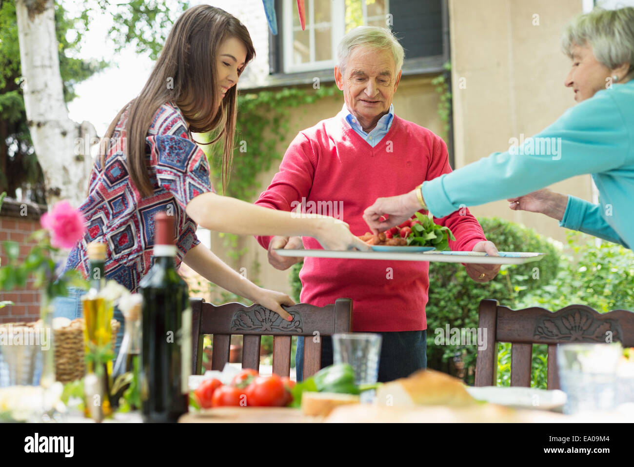 Young woman with grandparents setting the table - Stock Image