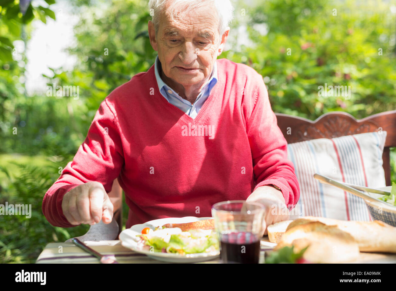 Senior man having lunch outdoors - Stock Image