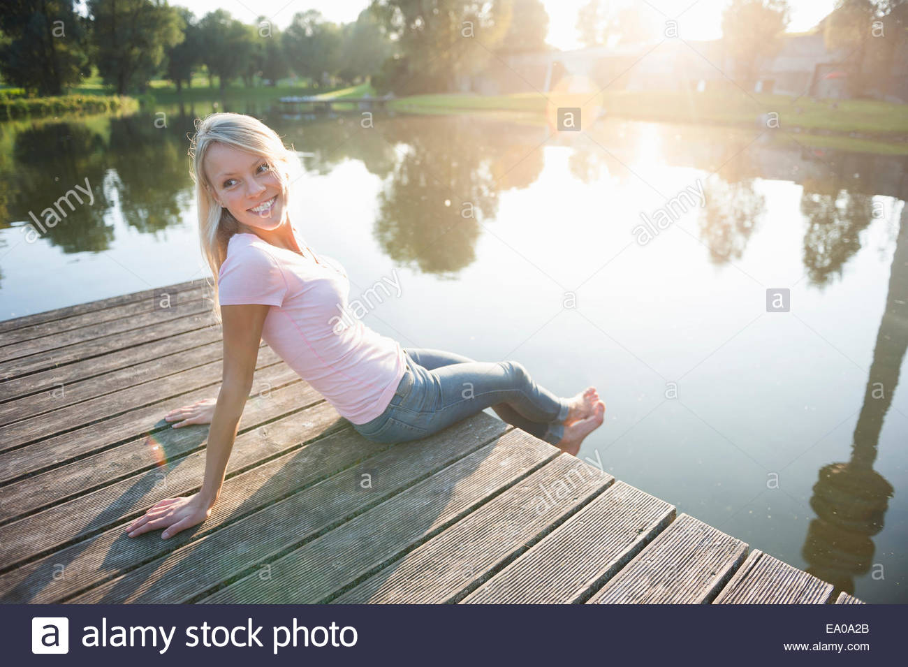 Young woman sitting on pier by lake - Stock Image