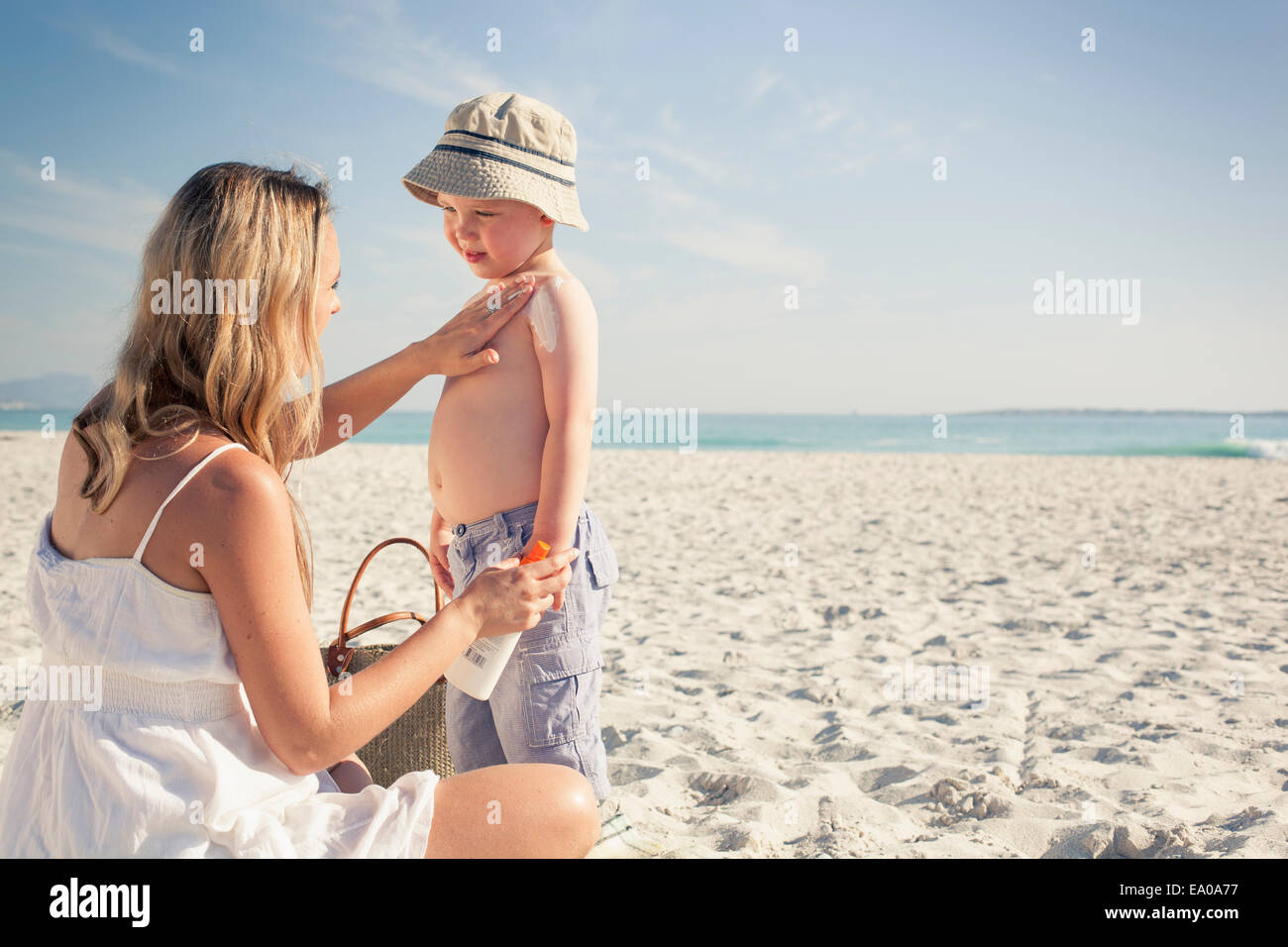 Mid adult mother applying sun lotion to young son on beach, Cape Town, Western Cape, South Africa - Stock Image