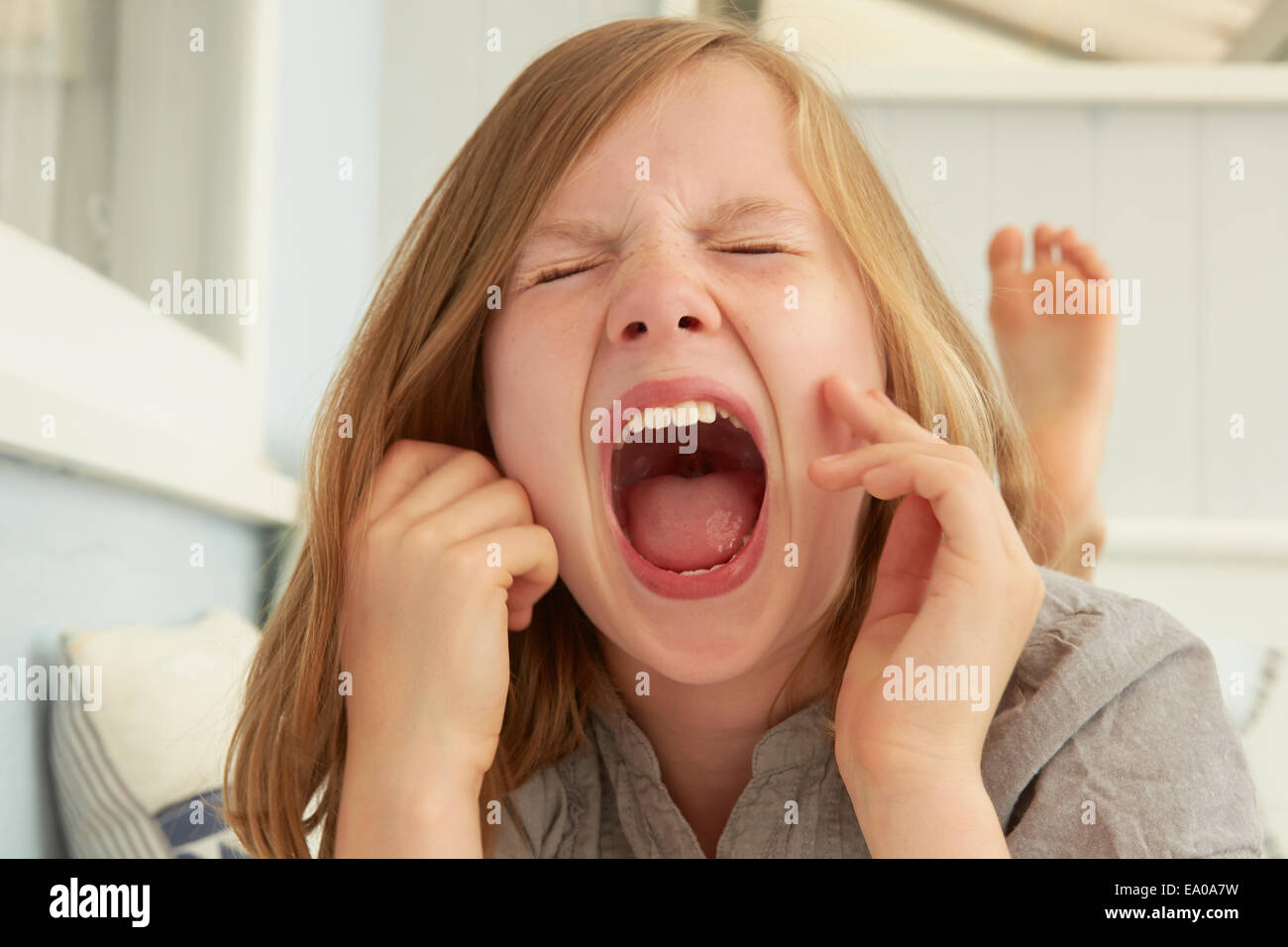 Girl with eyes closed screaming in holiday apartment - Stock Image