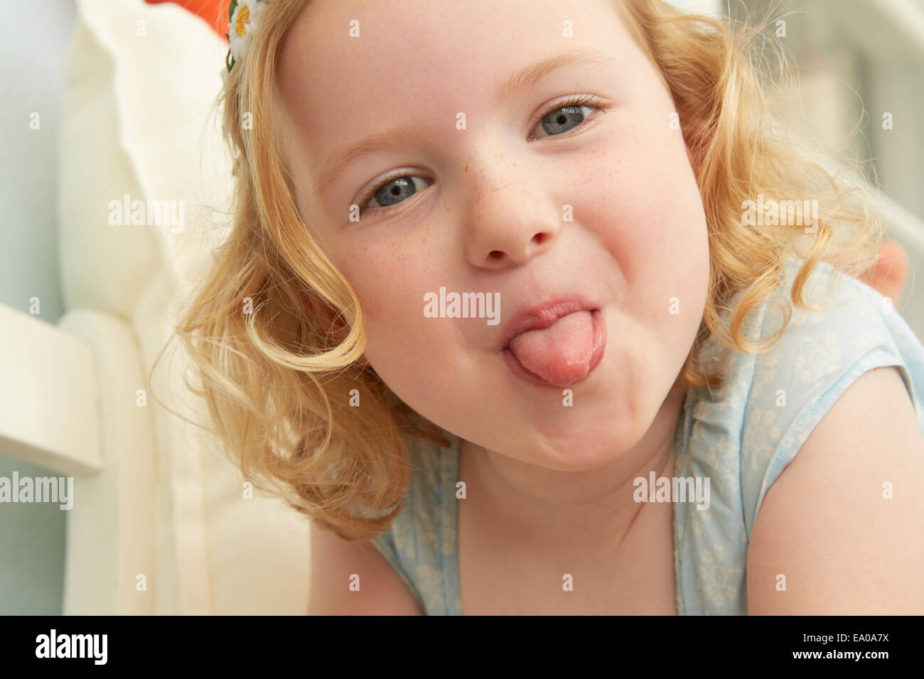 Portrait of girl lying on seat sticking tongue out - Stock Image