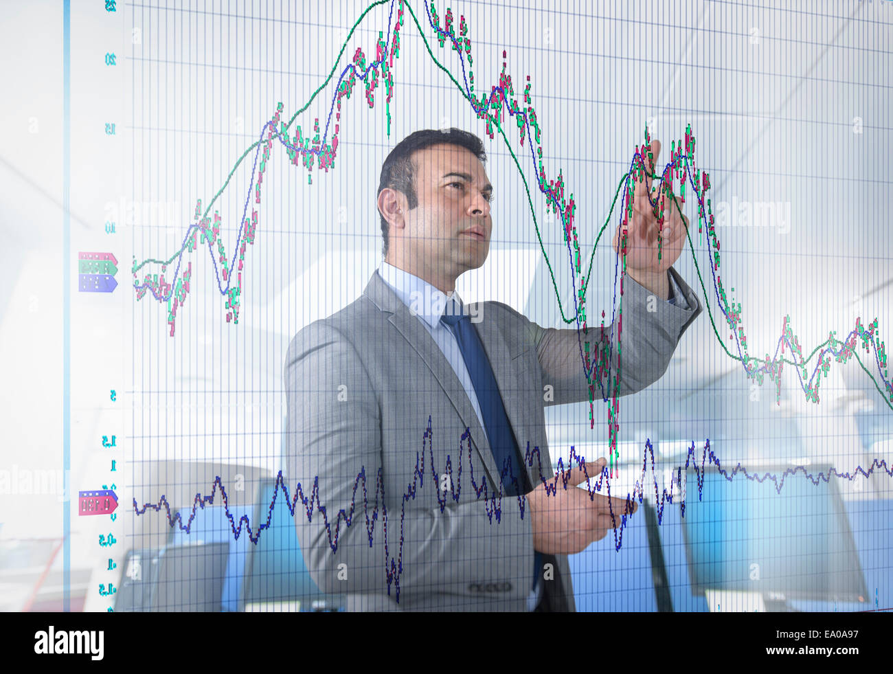 Asian businessman inspecting graph on interactive display - Stock Image