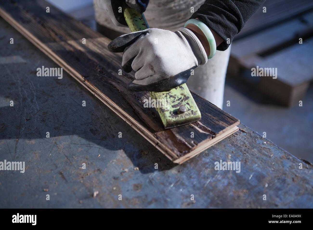 Carpenter working on wood plank in factory, Jiangsu, China - Stock Image