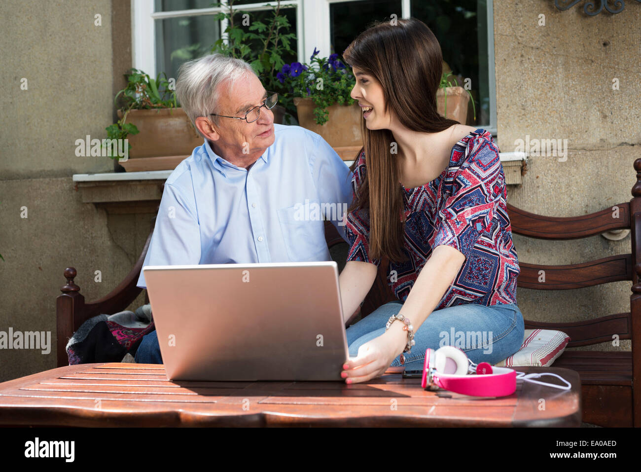 Young woman using laptop with grandfather - Stock Image