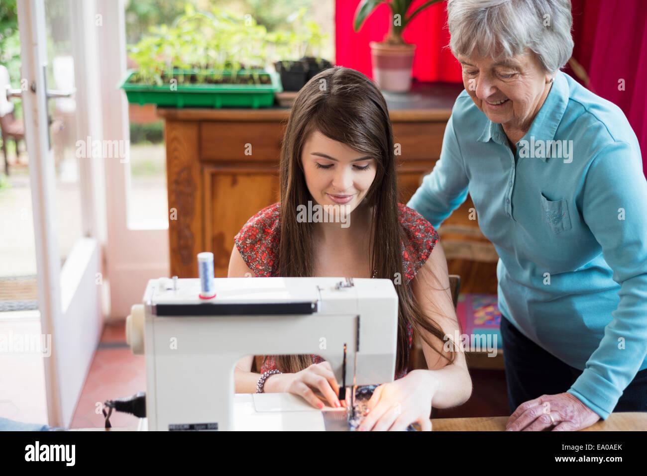 Senior woman watching granddaughter use sewing machine - Stock Image