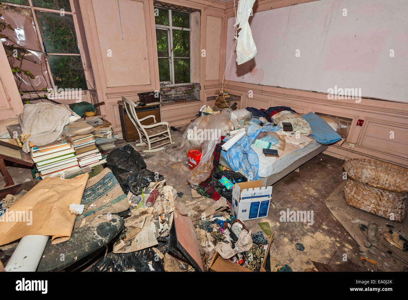 A chaotic bedroom room, filled with junk, in an abandoned house - Stock Image