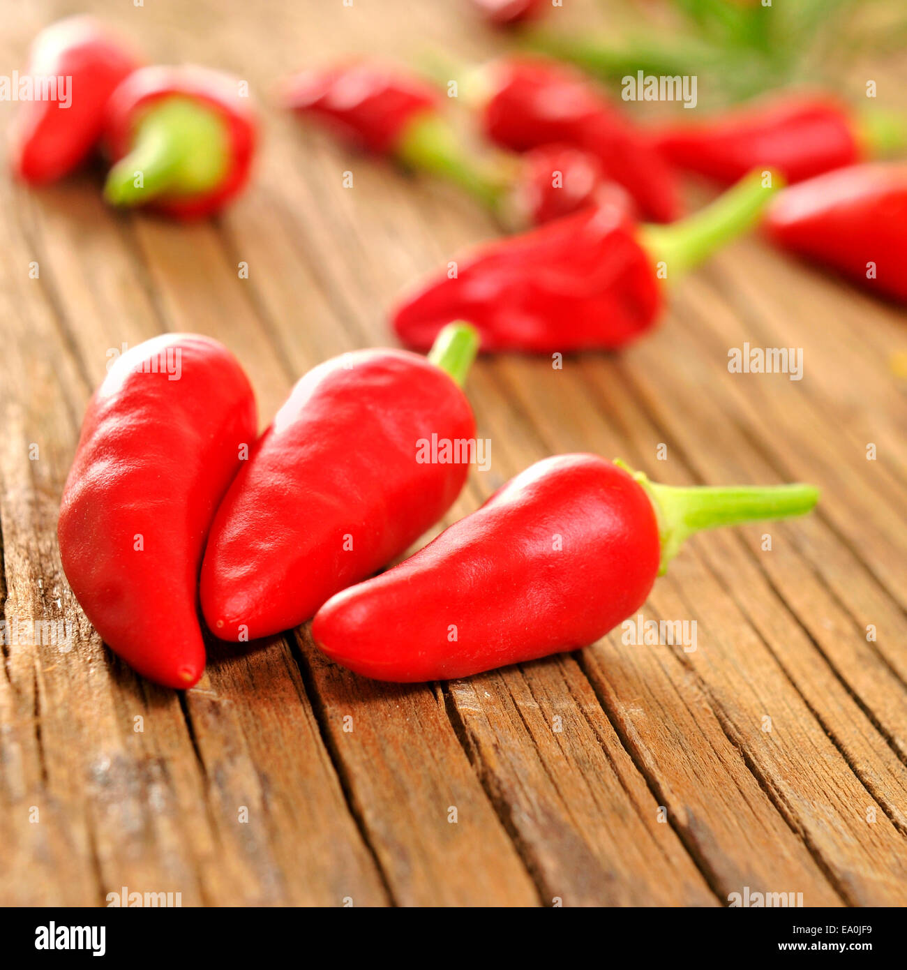 some small red peppers on a rustic wooden table - Stock Image