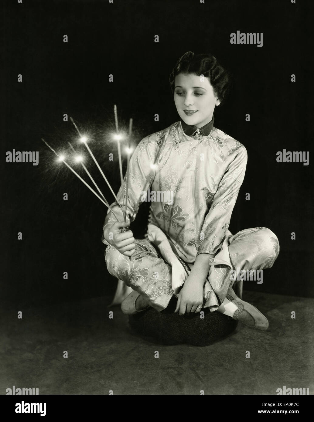 A woman holds sparklers - Stock Image