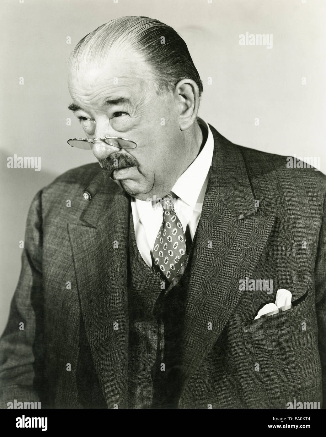 A man peers over the top of his pince-nez Stock Photo