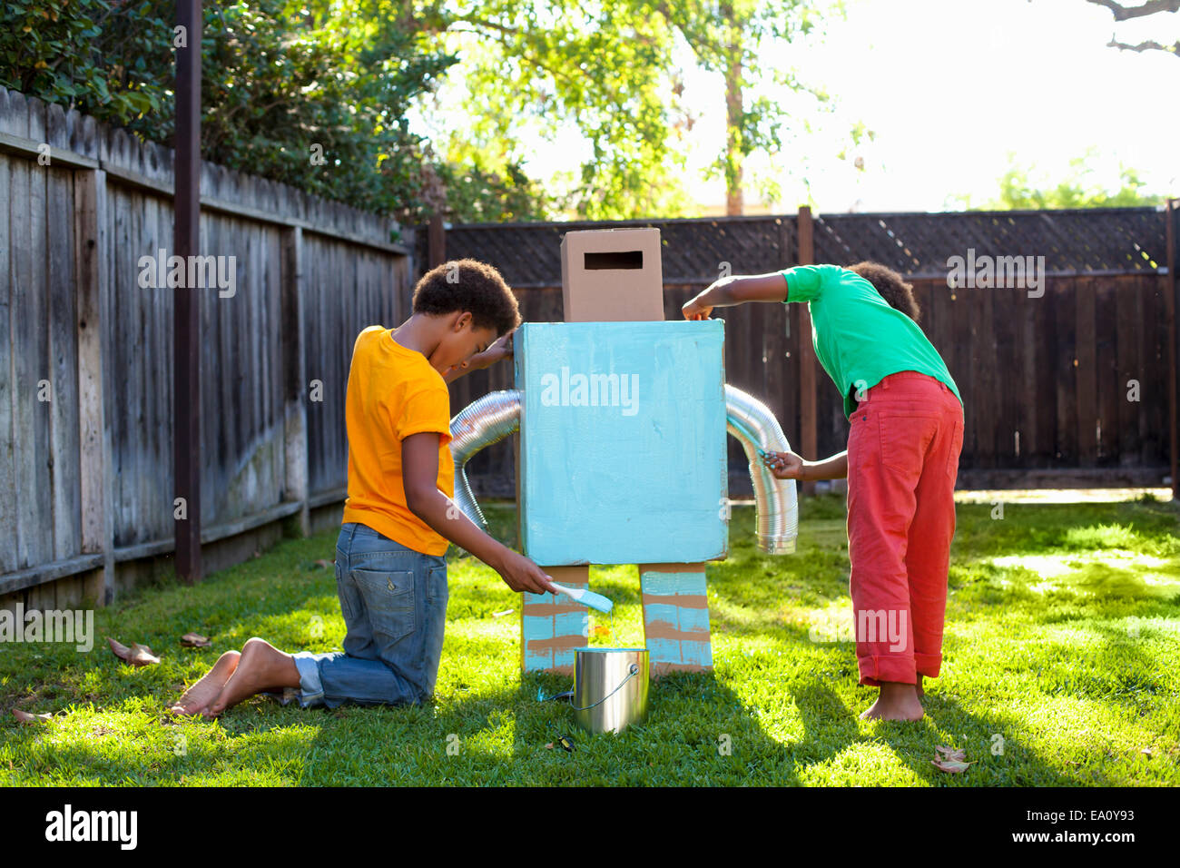 Two brothers painting home made robot light blue in garden - Stock Image