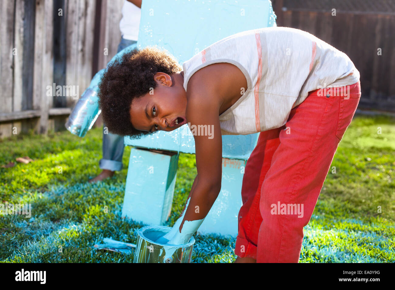 Boy dipping hands in blue paint in front of home made robot - Stock Image