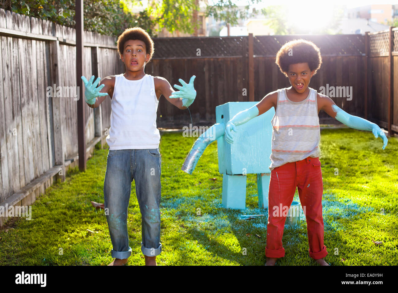 Portrait of two brothers in garden with light blue paint on hands and arms - Stock Image