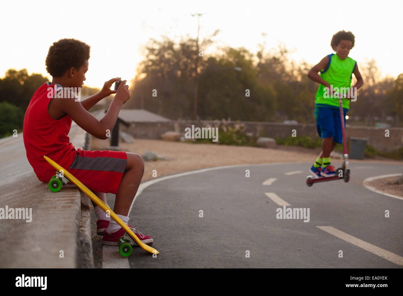 Boy photographing brother doing push scooter jump on road - Stock Image