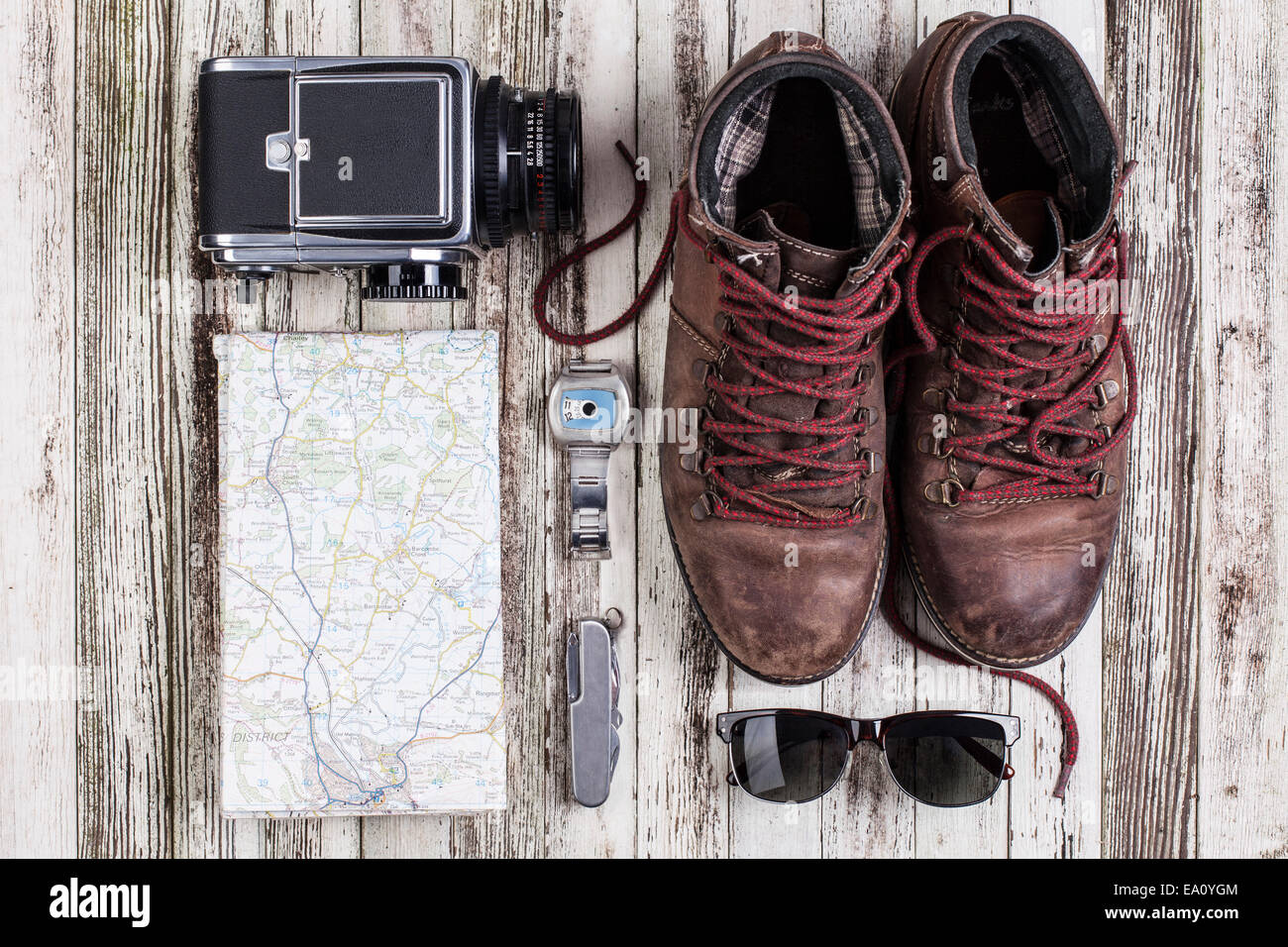 Still life of map with medium format camera and hiking boots - Stock Image