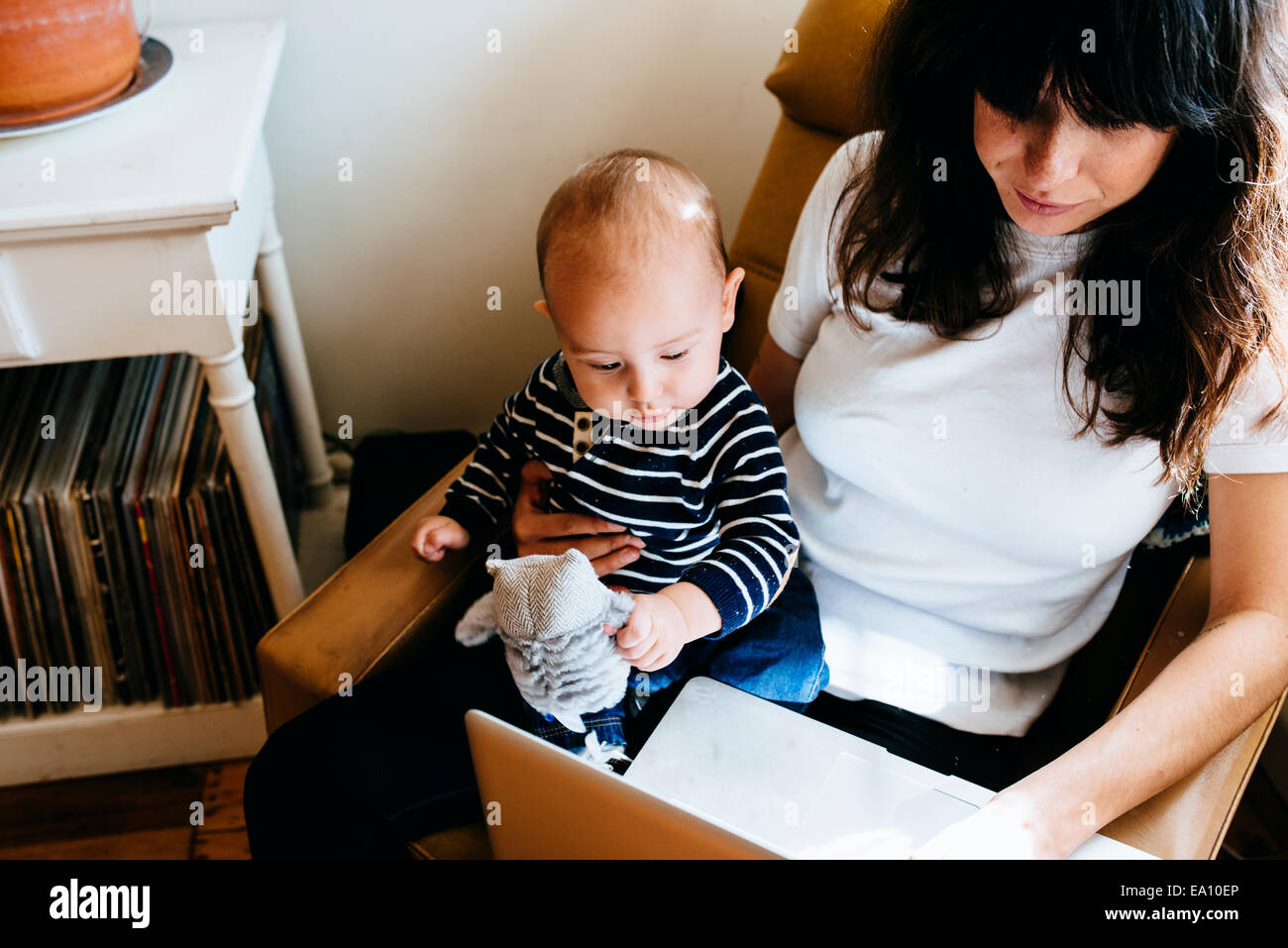 Mother using laptop with son on lap - Stock Image