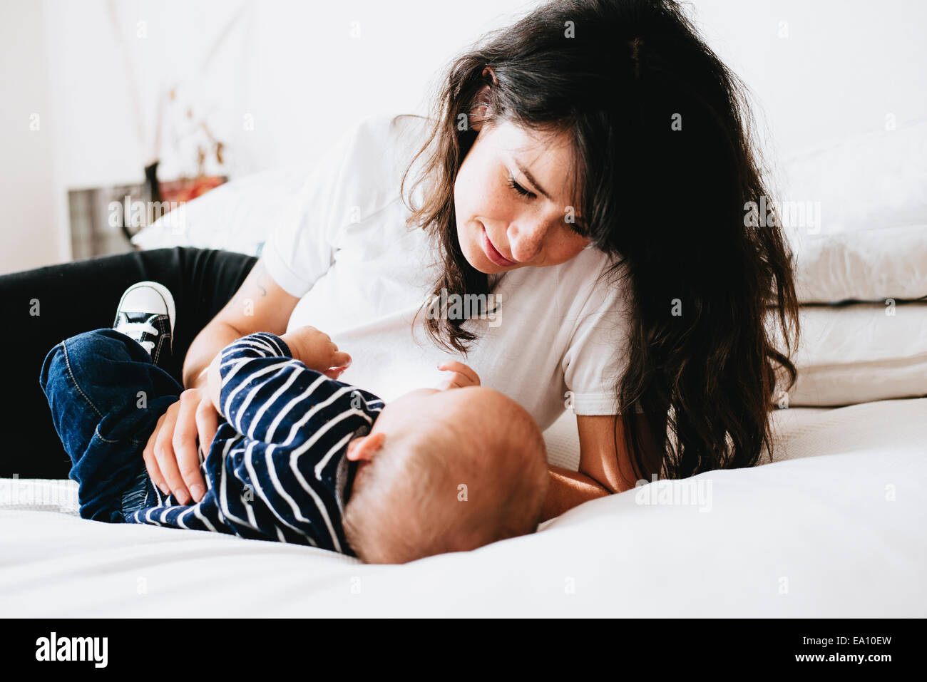 Mother looking down at son on bed - Stock Image