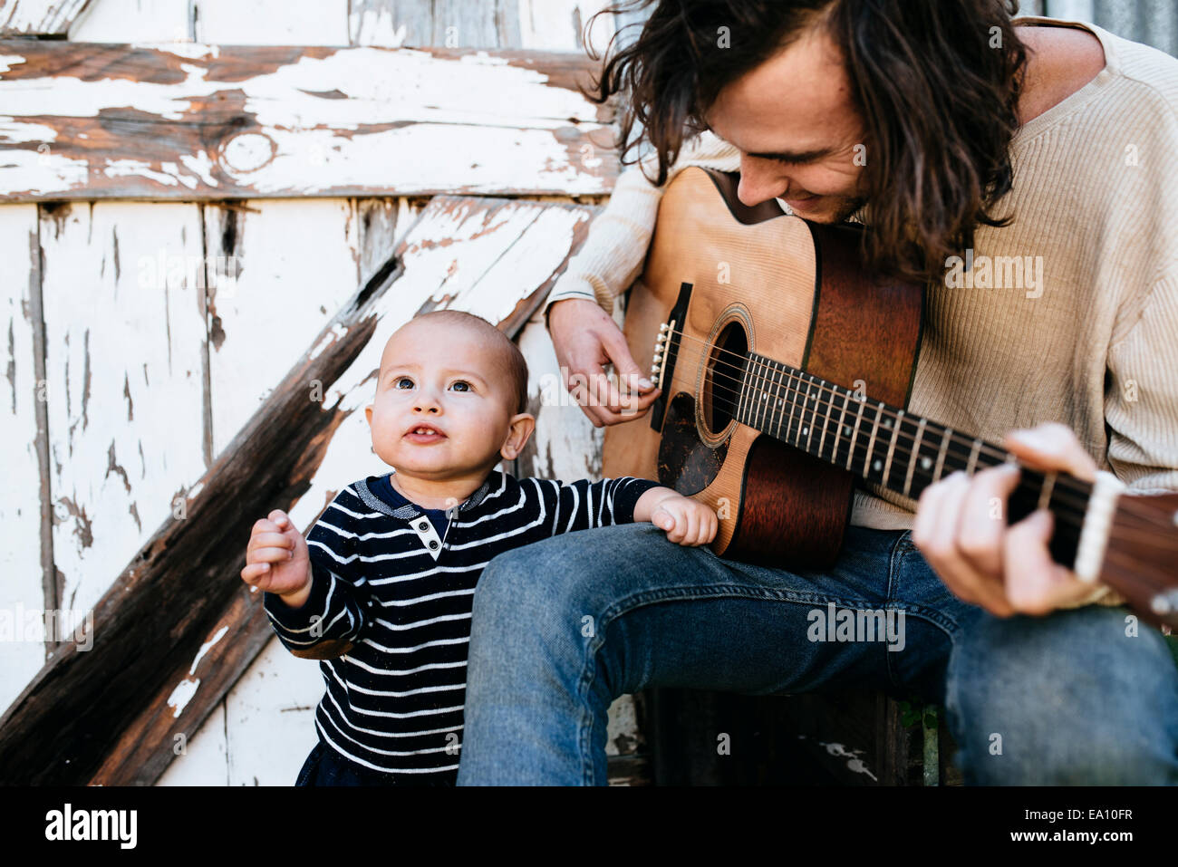 Father entertaining son with guitar - Stock Image