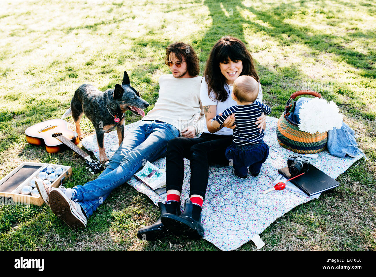 Couple with baby on picnic blanket in park - Stock Image