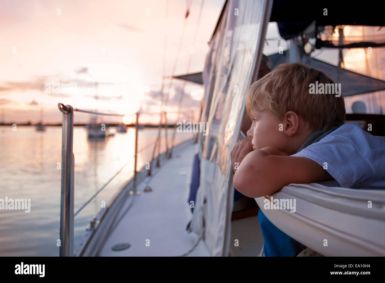 Boy gazing out to sea from sailboat at sunset - Stock Image