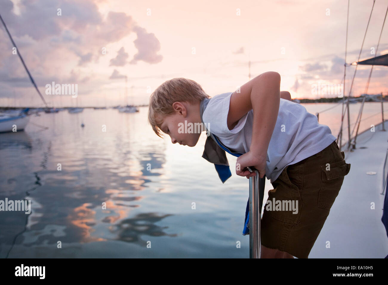 Boy on sailboat looking down to sea at sunset - Stock Image