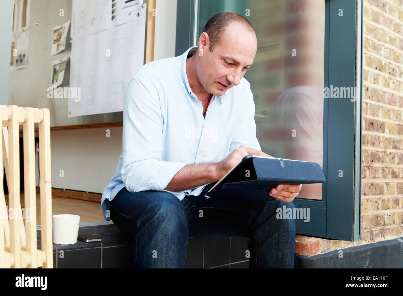 Male architect using touchscreen on digital tablet on office step Stock Photo