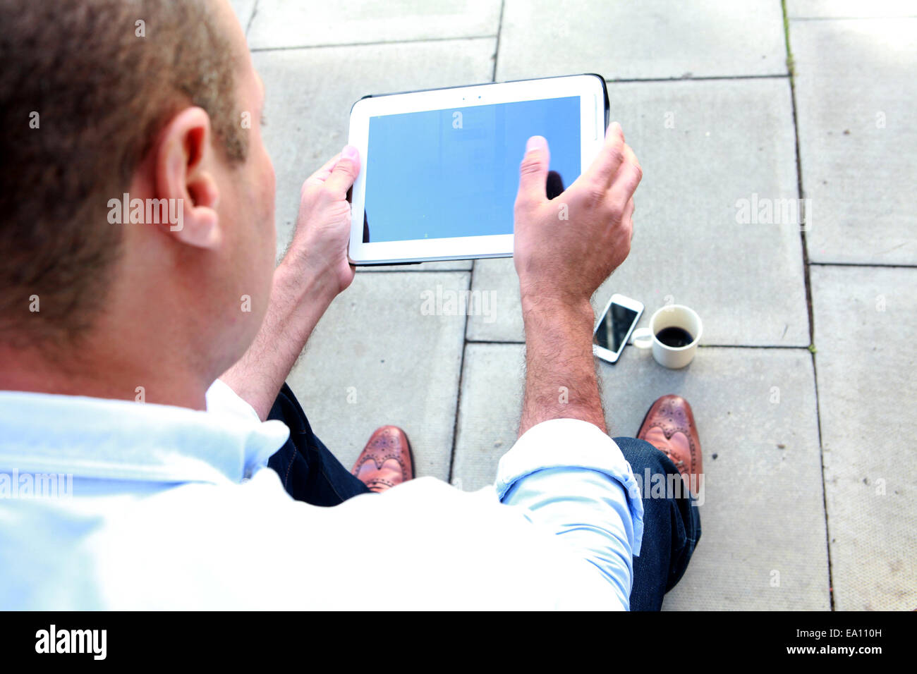 Over shoulder view of male architect digital tablet on office step - Stock Image