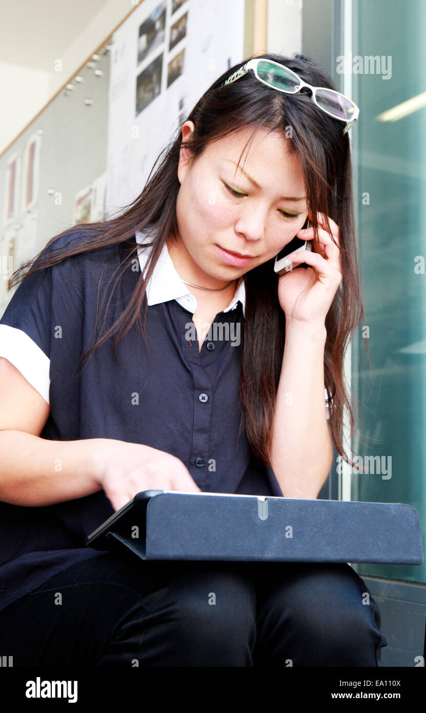 Female architect using smartphone and digital tablet on office step Stock Photo