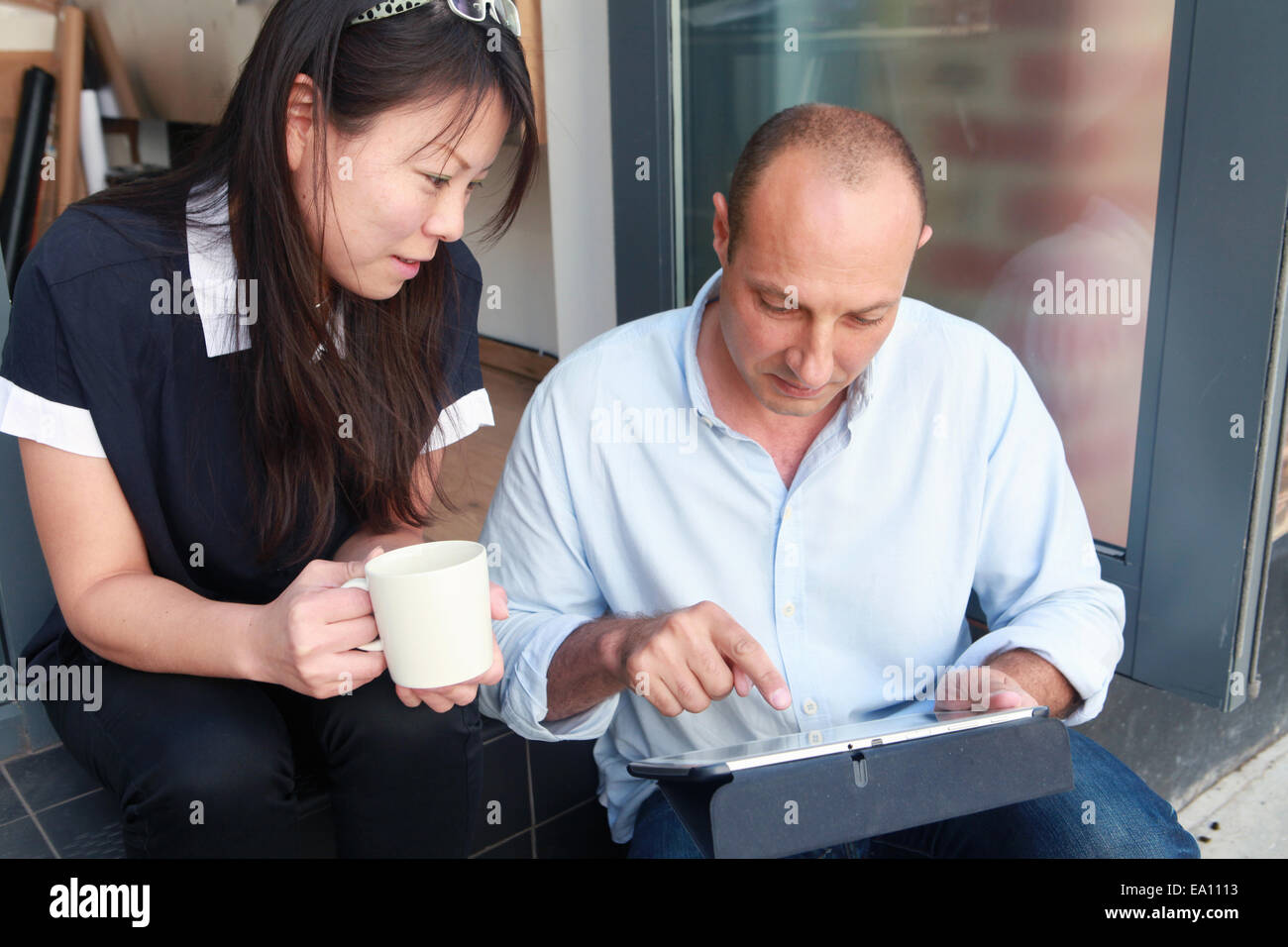 Two architect colleagues using at digital tablet on office step Stock Photo