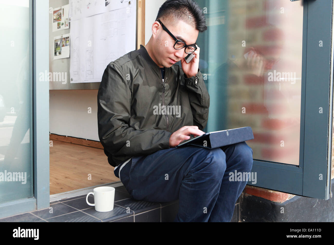 Male architect using smartphone and digital tablet on office step - Stock Image