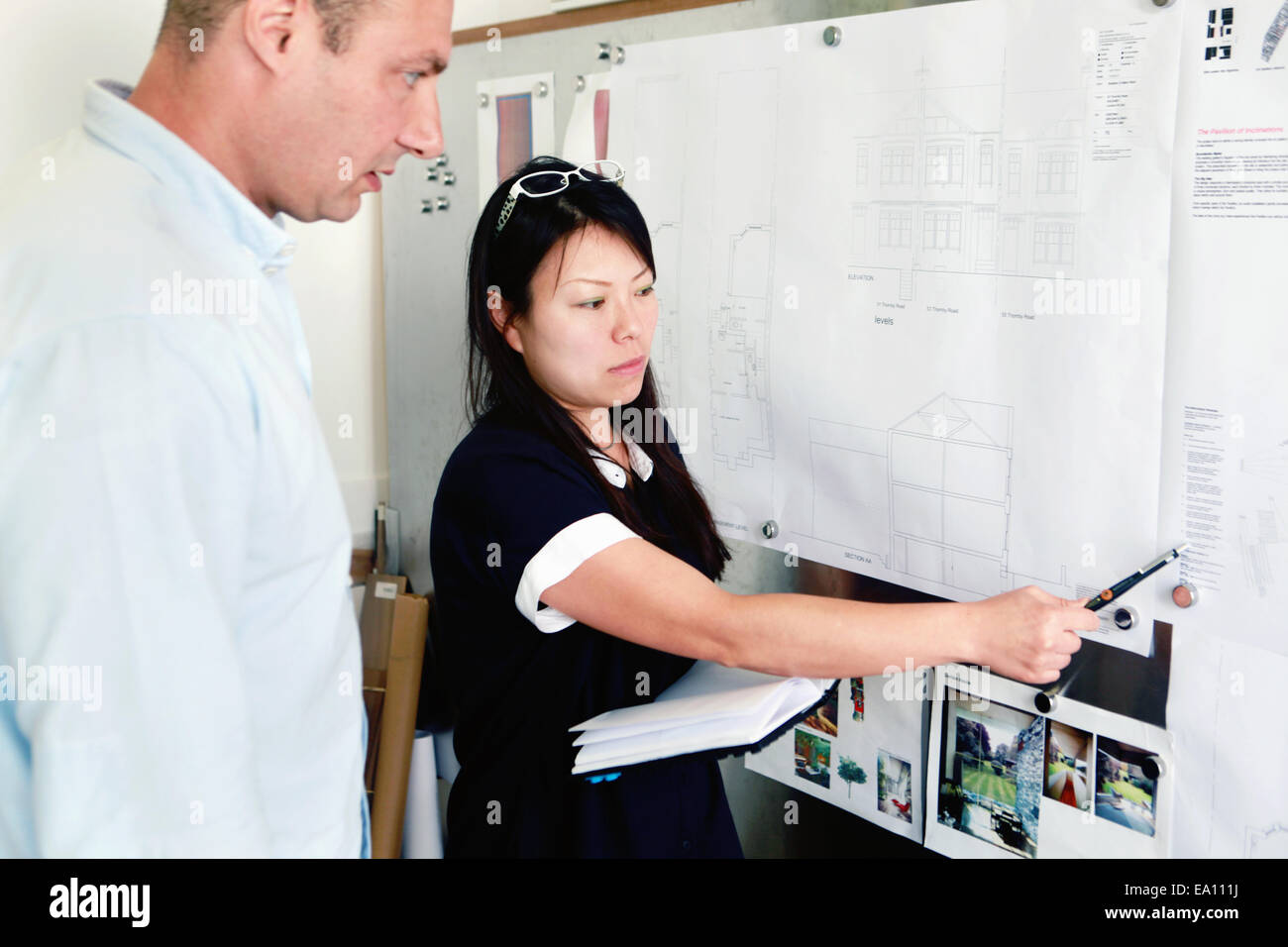 Male and female architects discussing ideas in office - Stock Image