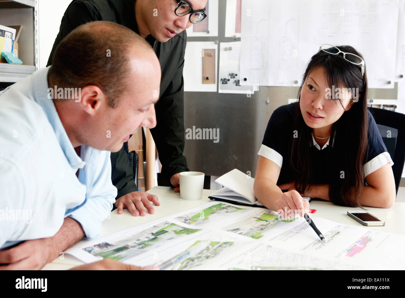 Team of three architects discussing ideas for blueprint in office - Stock Image