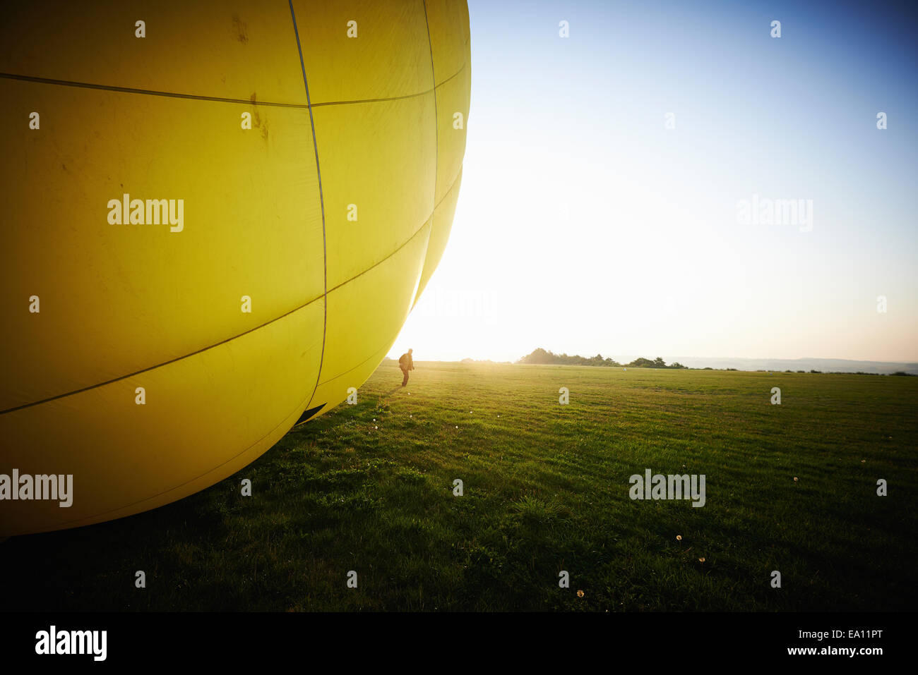 Inflated hot air balloon on field - Stock Image