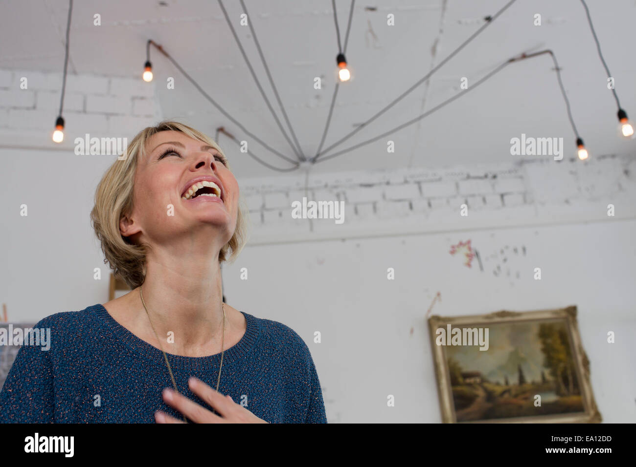 Mid adult woman laughing with head back - Stock Image